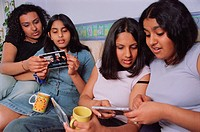 Group of teenage girls sitting on sofa, drinking tea and comparing CDs,