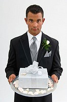 Groom with gift on silver platter