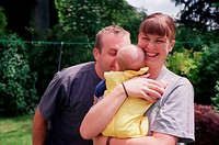 Mother and father standing outside in garden holding young baby smiling,