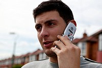 Young man outside using a mobile telephone,  for use in HIV and Aids,