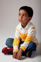 Young boy sitting cross legged on the floor