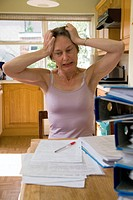 Teacher struggling with the pressure of a backlog of homework to mark