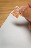Man putting US stamp on envelope