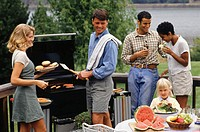 Two couples and one child (4-5) barbecuing on patio