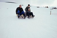 Father and two sons (8-9) sledding
