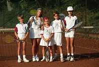 Group of children (6-11) standing by tennis net, portrait