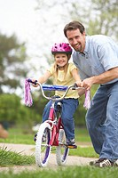 Father teaching daughter (4-6) to ride bicycle, portrait