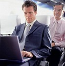 Businessman sitting on bus using laptop