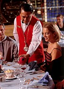 Waiter pouring wine into glass for couple sitting at table in restaurant