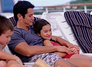 Father with daughter (12-13) and son (4-5) on deckchair