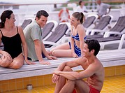 Two young couples sitting by pool on cruise ship, portrait