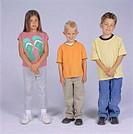 Three children (8-9) posing in studio, portrait
