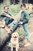 Two boys (8-13 years) with dog outdoors, smiling, portrait