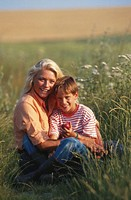 Mother with son (8-9) sitting in grass field, portrait