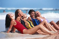 Women sitting on sand at beach