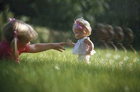 Girl (3-4) playing with doll on grass