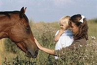 Mother carrying daughter (18-24 months) looking at horse, outdoors