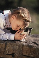 Girl (6-7) with kitten outdoors, eyes closed
