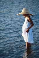 Girl (6-7) standing in water, side view