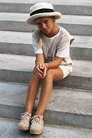 Girl (8-9) sitting on steps, portrait