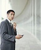 Businessman wearing earphones using mobile phone outside building