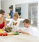 Mother and children (4-8) preparing salad at table, smiling