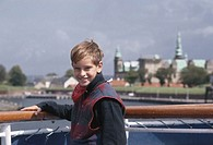 Boy (8-9) standing on deck, smiling
