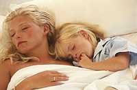 Mother with daughter (6-7) sleeping on bed, elevated view