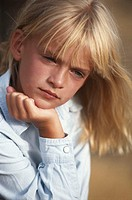 Girl (6-7) with hand on chin, close-up