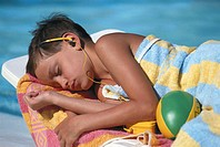 Boy (8-9) with personal stereo relaxing on sun lounger, eyes closed