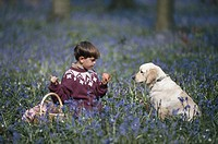 Boy (4-7) with dog sitting in flower field, holding apple