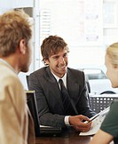 Businessman in meeting with woman and man, smiling