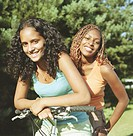 Young woman and teenage girl (13-15) riding bike, smiling, portrait