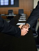 Two businessmen shaking hands in board room, close-up of hands