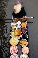 Thailand, Damnoen Saduak Floating Market, woman in boat with food