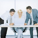 Two businessmen and young businesswoman using laptop, smiling