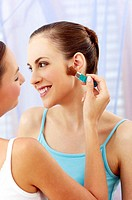 Woman applying makeup for her sister.