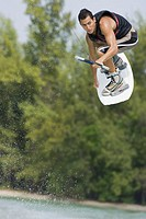 Young man performing jump on wakeboard
