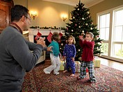 Father photographing three children (3-6) beside Christmas tree