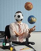 Businessman at desk juggling, ball obscuring face