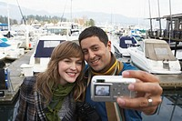 Couple digitally photographing selves on waterfront, smiling, close-up