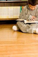 Boy (8-10) sitting on floor in front of bookshelf, reading book