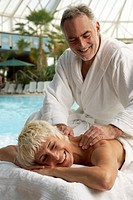 Mature couple by indoor pool, man massaging woman´s back, smiling