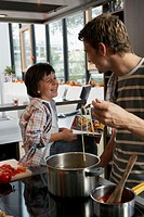 Boy (5-7) on kitchen worktop smiling at father cooking spaghetti