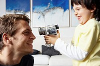 Boy (5-7) filming father with camcorder, side view