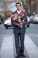 Young man on zebra crossing, holding boquet of flowers, portrait