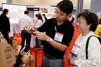 Convention Center, Americas Food and Beverage Show, Asian couple, hot sauce. Miami Beach. Florida. USA.