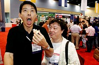 Convention Center, Americas Food and Beverage Show, Asian man reacts, hot sauce, woman watches. Miami Beach. Florida. USA.