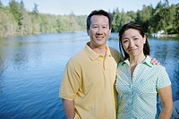 Portrait of couple smiling with lake behind them