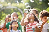 Children outdoors blowing bubbles